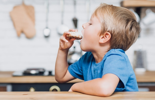 Ragazzo di vista laterale che mangia un biscotto