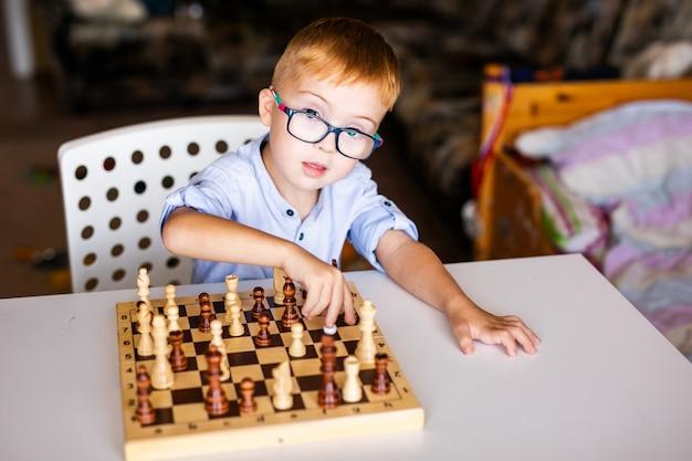 Ragazzo di zenzero con sindrome di down con grandi occhiali che giocano a scacchi a casa