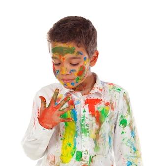 Ragazzo divertente con le mani e la faccia piena di vernice