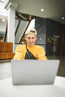 Ragazzo divertente in abiti da strada alla moda sta lavorando su un computer portatile al tavolo di un centro commerciale
