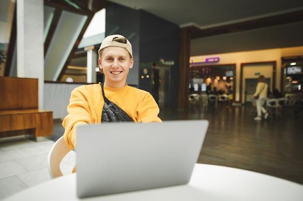 Ragazzo divertente in abiti da strada alla moda sta lavorando su un computer portatile in un centro commerciale