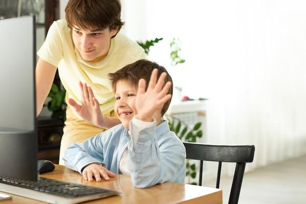 Ragazzo e adolescente sorridenti che chiacchierano online e che ondeggiano allo schermo di computer.