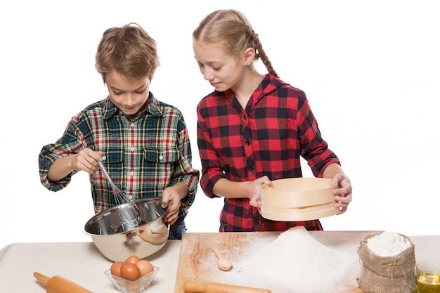 Ragazzo e ragazza a fare la pasta per cuocere, fratello e sorella, ragazzo panna da montare, ragazza setacciare la farina, su sfondo bianco, isolare