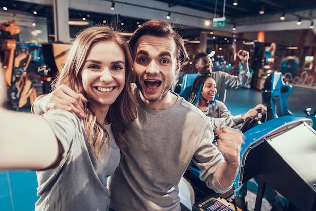 Ragazzo e ragazza bionda in sala giochi. la coppia sta prendendo selfie.