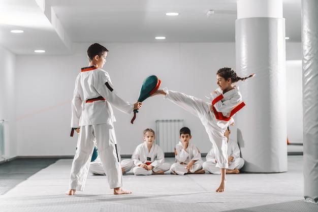 Ragazzo e ragazza caucasici in dobok che hanno addestramento di taekwondo in palestra. ragazza che dà dei calci mentre ragazzo che tiene il bersaglio di scossa.