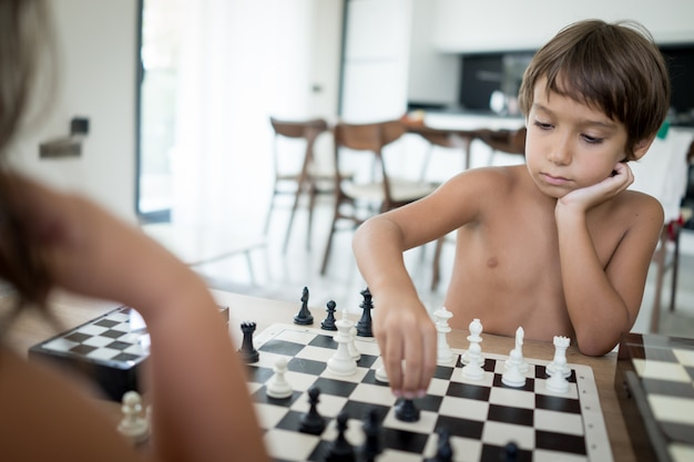 Ragazzo e ragazza che giocano a scacchi a casa