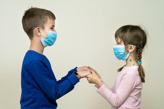 Ragazzo e ragazza che indossano la maschera medica protettiva blu malata con varicella, morbillo o virus della rosolia con eruzioni cutanee sul corpo. protezione dei bambini durante l'epidemia di coronovirus. concetto di contagio covid-19.