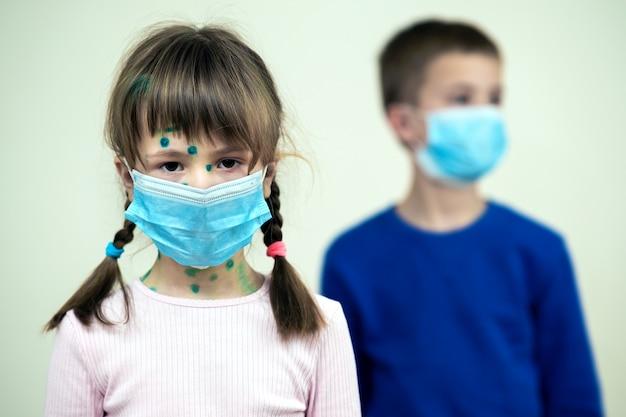 Ragazzo e ragazza che indossano le maschere mediche protettive blu