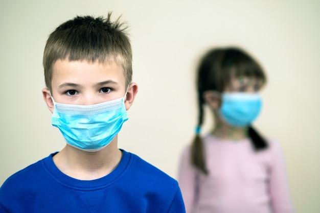 Ragazzo e ragazza che indossano le maschere mediche protettive blu.
