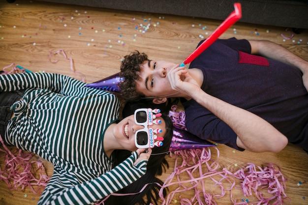 Ragazzo e ragazza che pongono sul pavimento
