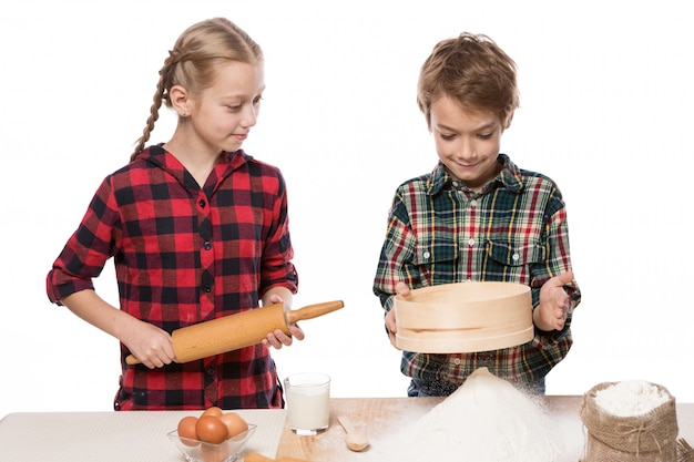 Ragazzo e ragazza che producono pasta per cottura, fratello e sorella, ragazzo che setaccia farina, ragazza che guarda, su fondo bianco, isolato