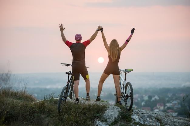 Ragazzo e ragazza con le biciclette da montagna tengono le mani alzate verso l'alto