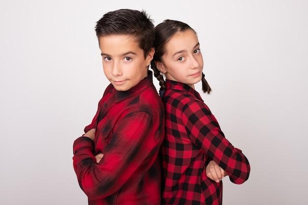 Ragazzo e ragazza con le braccia incrociate in posa schiena contro schiena con sguardo impegnativo
