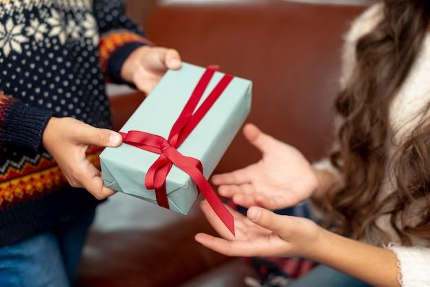 Ragazzo e ragazza del primo piano che dividono i regali