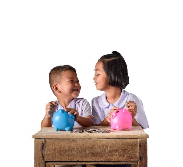 Ragazzo e ragazza di paese asiatici svegli che mettono le monete nel porcellino salvadanaio isolato su fondo bianco