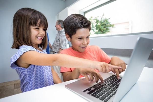 Ragazzo e ragazza felici che per mezzo del computer portatile