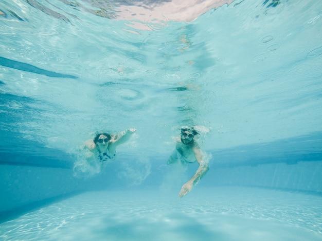 Ragazzo e ragazza immersioni in piscina