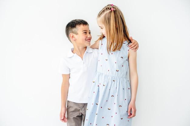 Ragazzo e ragazza sorridenti che abbracciano i bambini