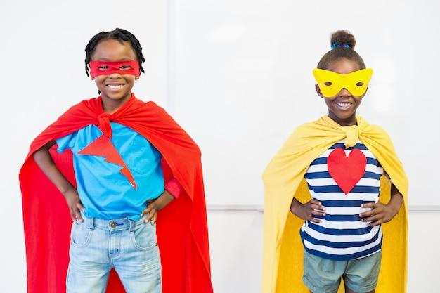 Ragazzo e ragazza sorridenti che fingono di essere un supereroe