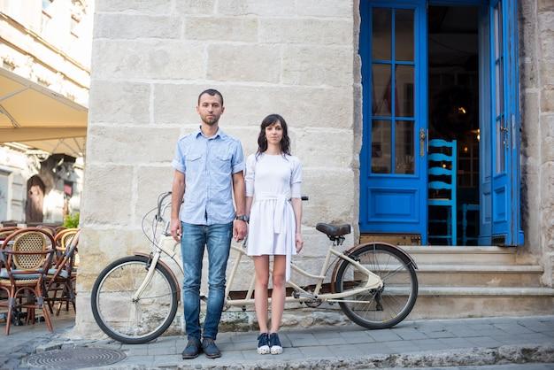 Ragazzo e ragazza vicino alla bici in tandem, alle pareti e alla porta d'annata