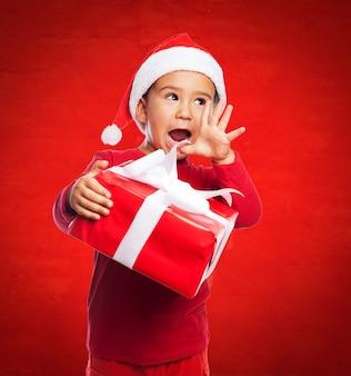 Ragazzo emozionante in possesso di un regalo con il nastro bianco