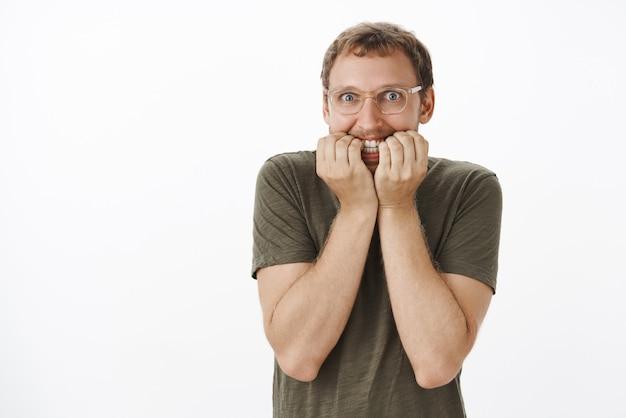 Ragazzo europeo divertente impaziente che ha dipendenza facendo scommesse e in attesa di risultati che si morde nervosamente le unghie e sorride con espressione eccitata ed elettrizzata fissando con sguardo folle