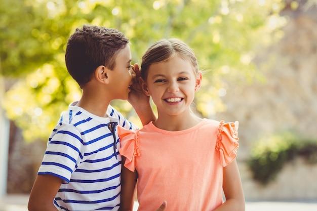 Ragazzo felice che bisbiglia un segreto nell'orecchio delle ragazze