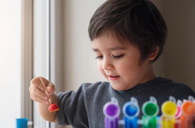 Ragazzo felice che dipinge colore di acqua su carta, spazzola di arte della tenuta del bambino che impara pittura e drawi