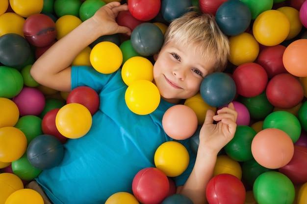 Ragazzo felice che gioca in piscina di palline