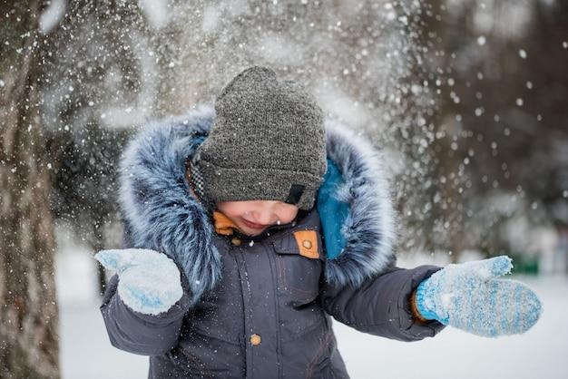 Ragazzo felice che gioca nella neve, giochi invernali