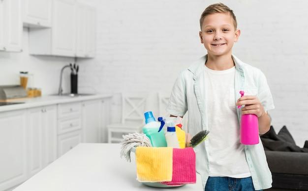 Ragazzo felice che posa mentre tenendo i prodotti di pulizia