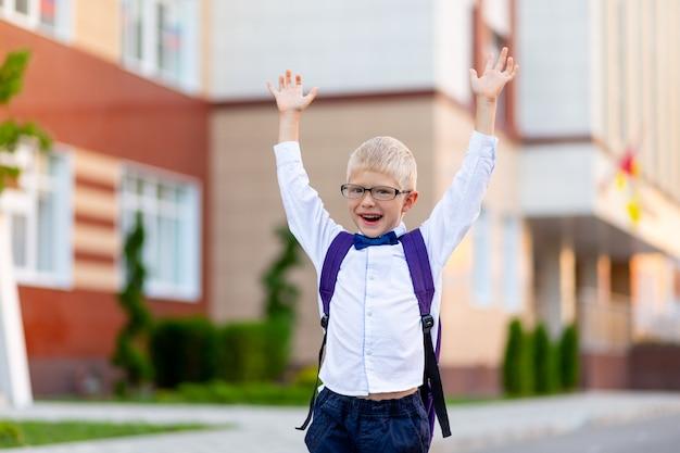 Ragazzo felice con gli occhiali e una valigetta è felice con le mani in alto vicino alla scuola