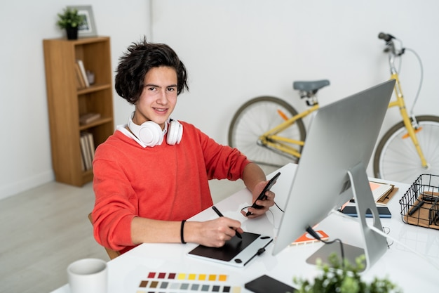 Ragazzo felice con lo stilo e lo smartphone che ti guarda mentre usi la tavoletta grafica davanti allo schermo del computer