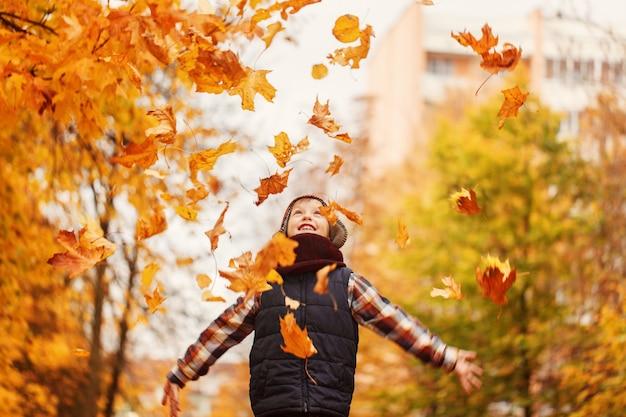 Ragazzo felice del bambino che getta il livello caduto su, giocando nel parco di autunno.