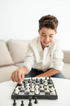 Ragazzo felice del colpo medio che gioca scacchi