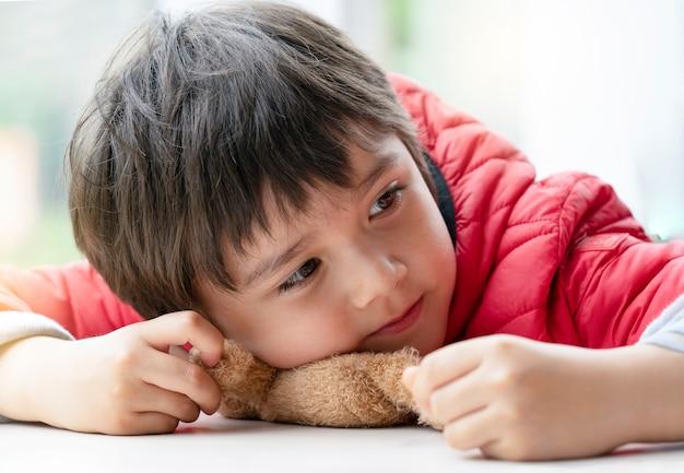 Ragazzo felice del ritratto del bambino che gioca con l'orsacchiotto che mette su tavola