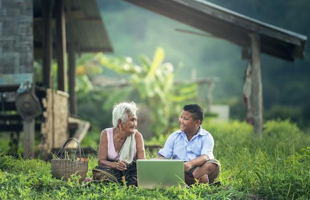 Ragazzo felice e nonna che per mezzo di un computer portatile all'aperto