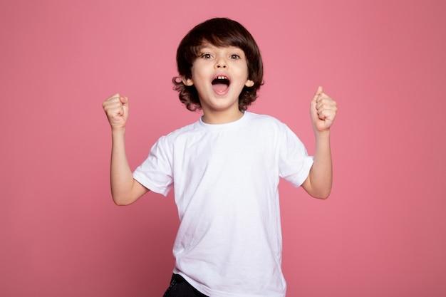 Ragazzo felice piccolo adorabile sveglio in maglietta e blue jeans bianche sul rosa