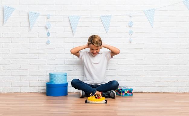 Ragazzo festeggia il suo compleanno con una torta che copre entrambe le orecchie con le mani