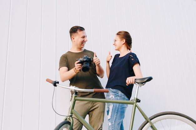 Ragazzo-fotografo alla moda e bella donna che mostrano un pollice in su, mentre si guardano, in piedi con la bici retrò, dopo aver scattato foto all'aperto.