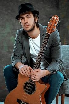 Ragazzo freddo che si siede con la chitarra su spazio grigio