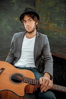 Ragazzo freddo che si siede con la chitarra sul gray