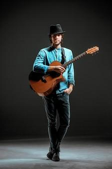 Ragazzo freddo in piedi con la chitarra su sfondo scuro