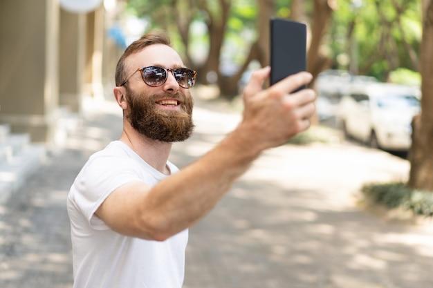 Ragazzo gioioso hipster prendendo selfie