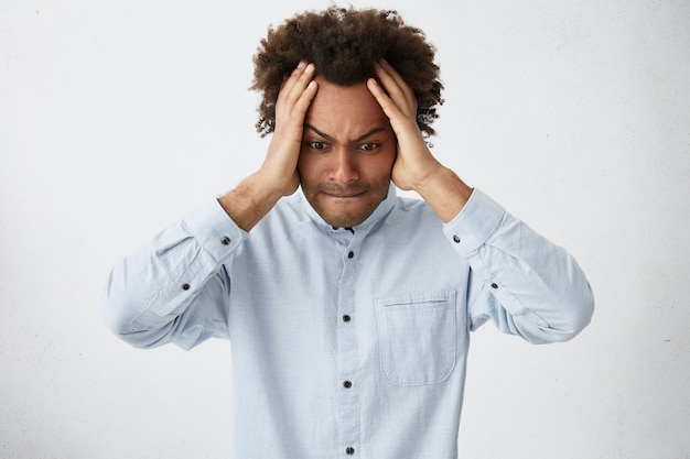 Ragazzo giovane hipster dalla carnagione scura indossa una camicia bianca tenendo le mani sulla testa guardando disperatamente verso il basso