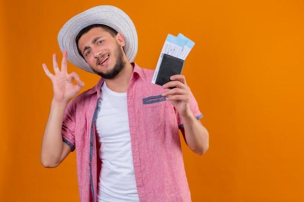 Ragazzo giovane viaggiatore bello con cappello estivo in possesso di biglietti aerei guardando la fotocamera uscita e felice sorridente allegramente facendo segno ok pronto a viaggiare in piedi su sfondo arancione