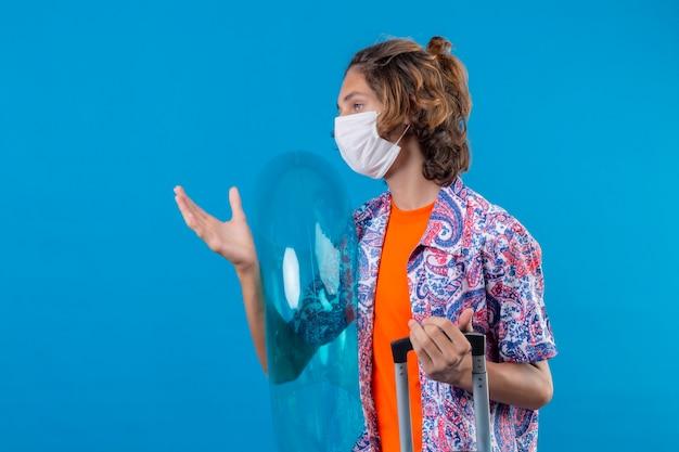 Ragazzo giovane viaggiatore che indossa la maschera protettiva facciale che tiene la valigia di viaggio e l'anello gonfiabile che osserva da parte con l'espressione sicura seria che sta con il braccio alzato sopra fondo blu