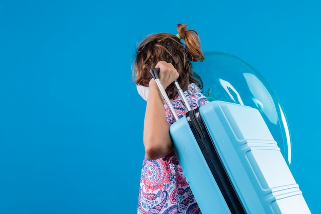 Ragazzo giovane viaggiatore che indossa la maschera protettiva per il viso tenendo la valigia di viaggio e anello gonfiabile in piedi lateralmente lasciando su sfondo blu
