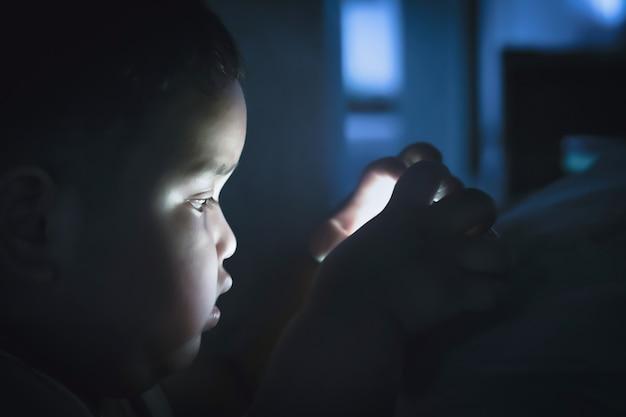 Ragazzo grasso che gioca smartphone in camera da letto alla notte su fondo scuro. il gioco prolungato del telefono influisce negativamente sulla vista e sulla salute dei bambini piccoli.