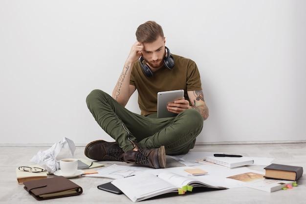 Ragazzo hipster alla moda concentrato con le braccia tatuate, siede a gambe incrociate sul pavimento, circondato da molti libri e carte